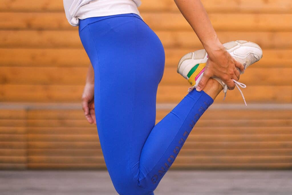 A person stretching feet while wearing blue leggings