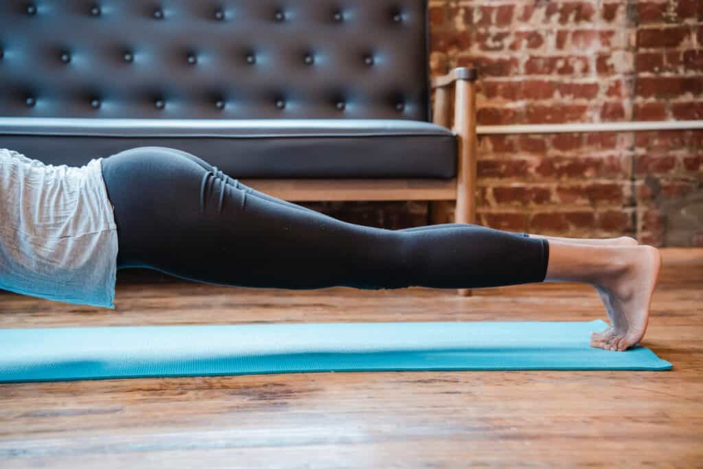 A person on a yoga mat wearing leggings