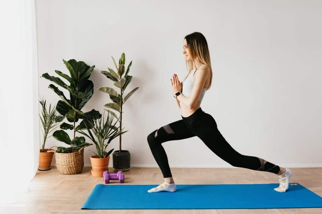 A person wearing black leggings while doing yoga