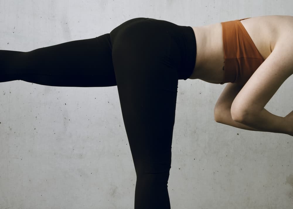 A person wearing leggings while doing stretches