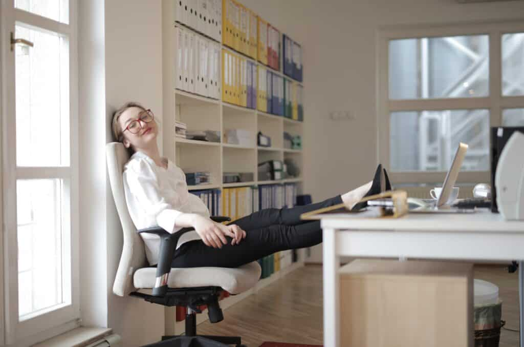 A woman in work with feet on table displaying leggings