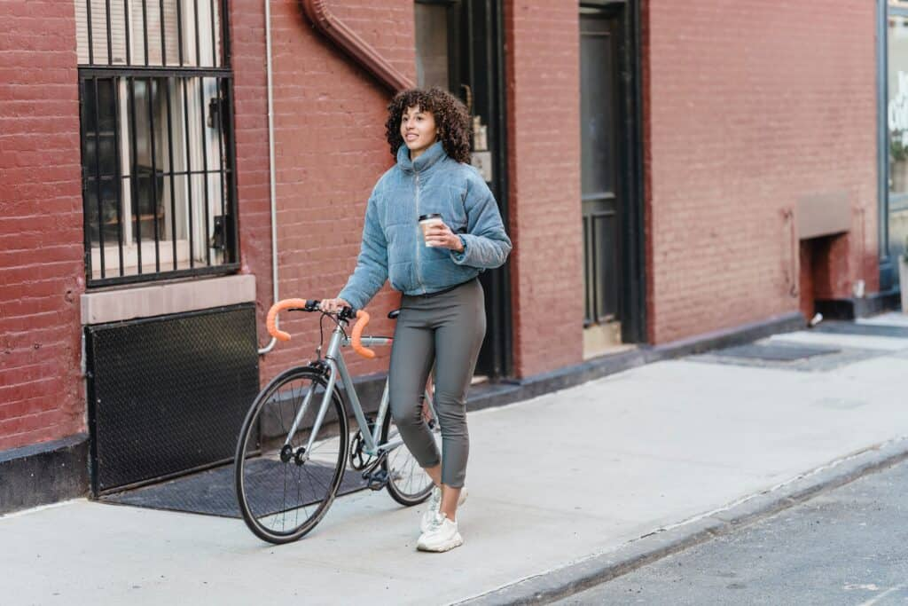 A woman wearing leggings bringing a bicycle to work