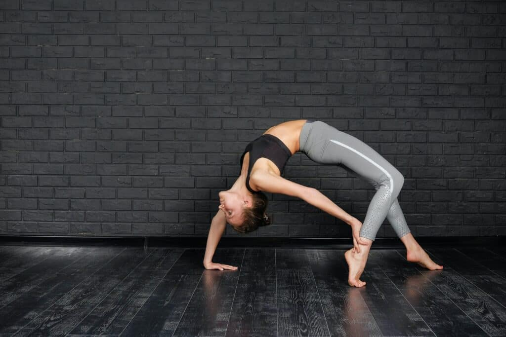 a woman wearing gray leggings stretching her back