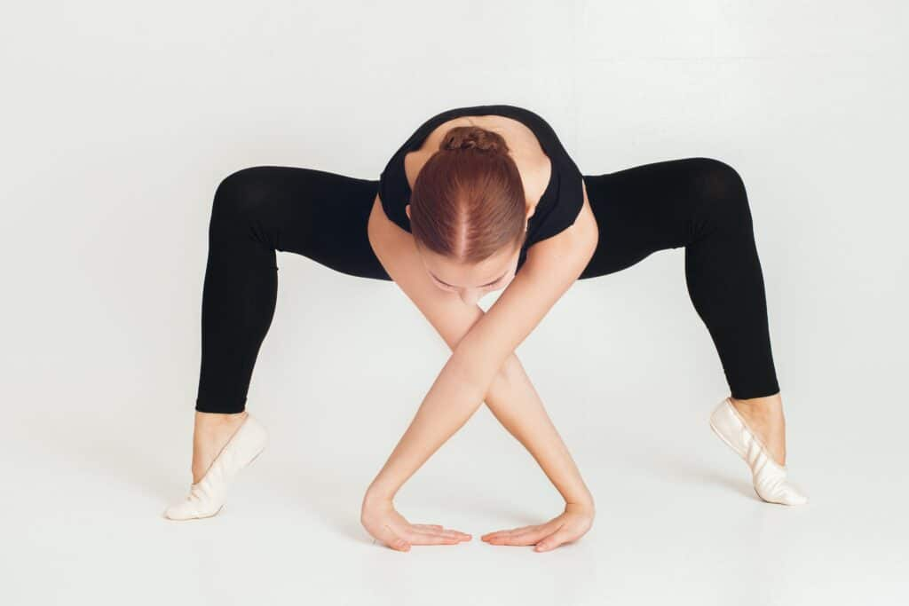 A woman wearing black leggings while stretching