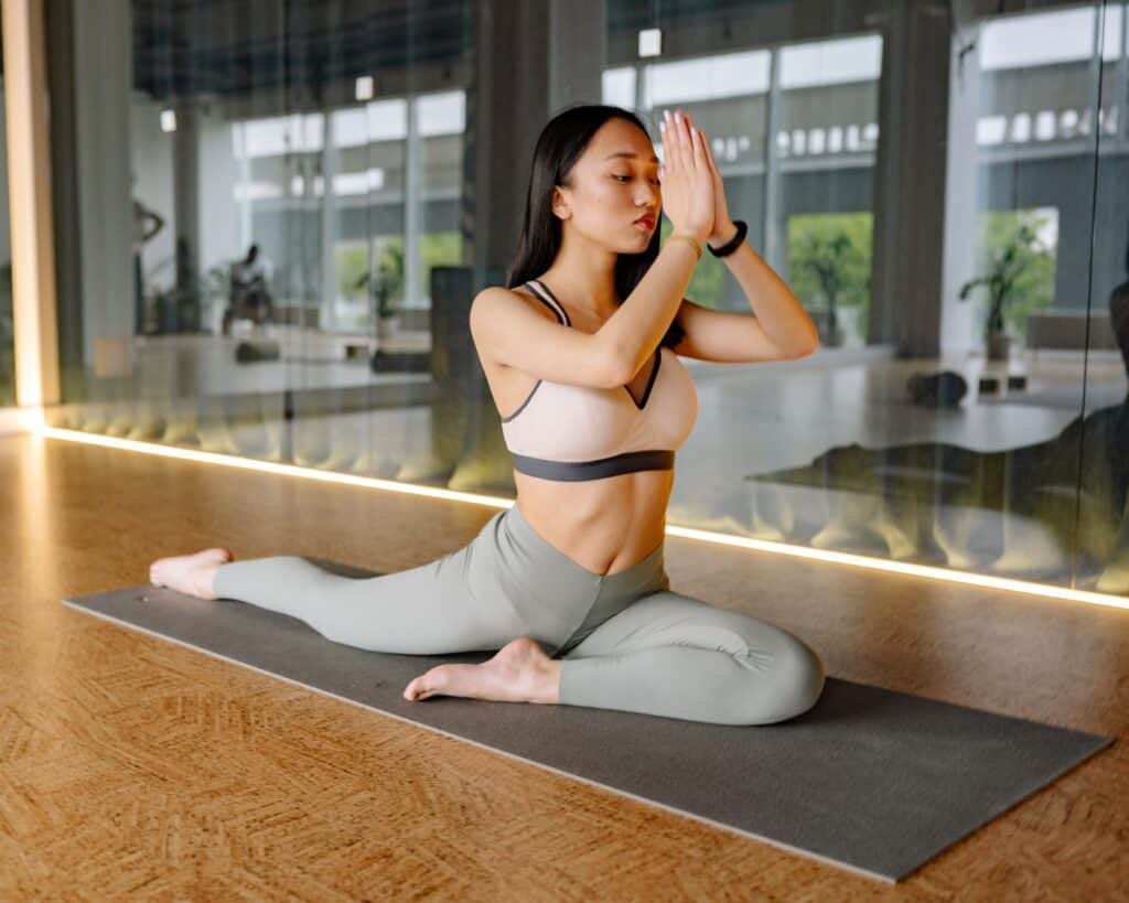 a woman stretching on a yoga mat wearing gray leggings