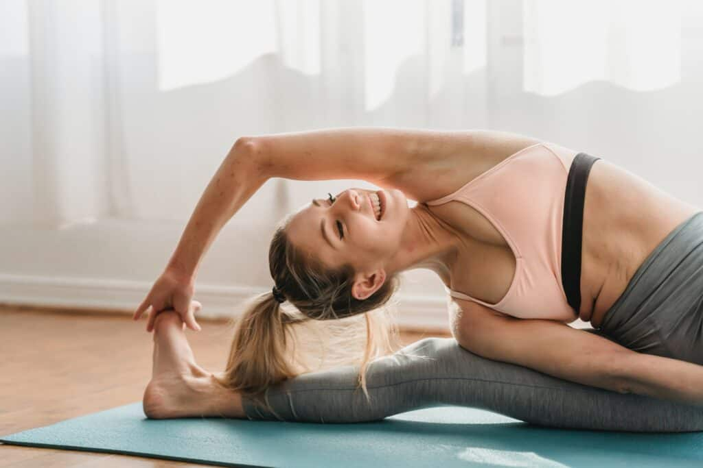 a woman stretching on her side wearing a gray leggings