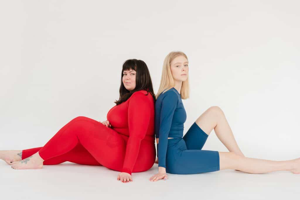 two women sitting behind each other wearing a red and blue postpartum leggings