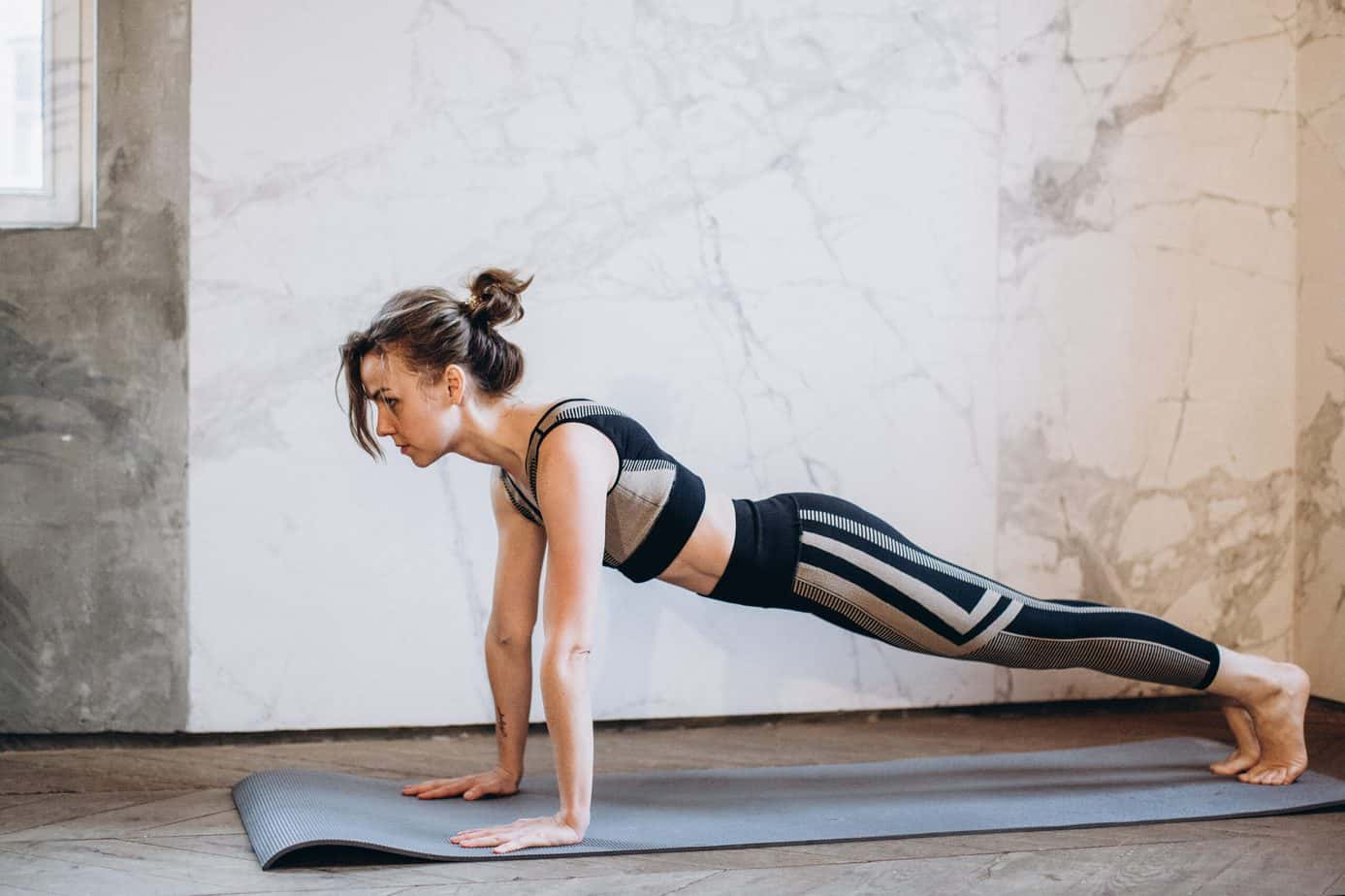 a woman doing a basic plank wearing a see though black leggings