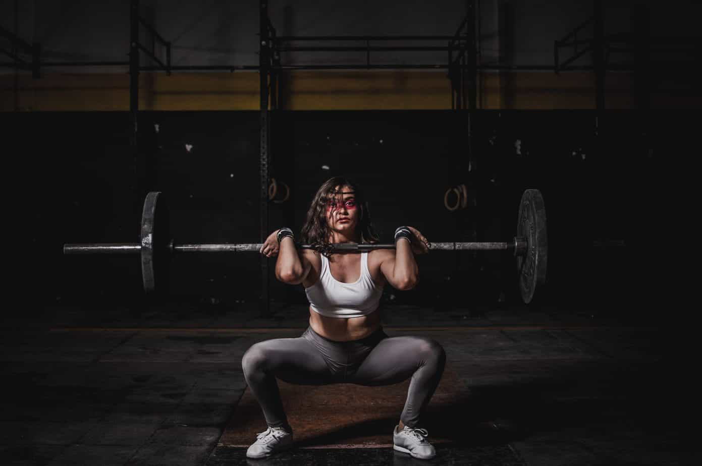 A woman wearing a gray leggings while squatting
