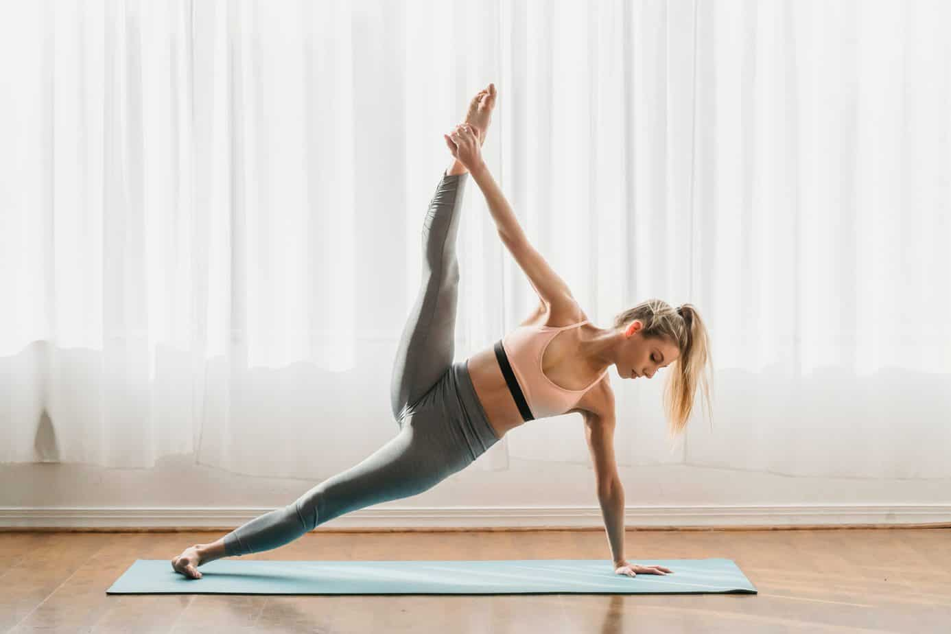 A woman wearing yoga leggings while stretching