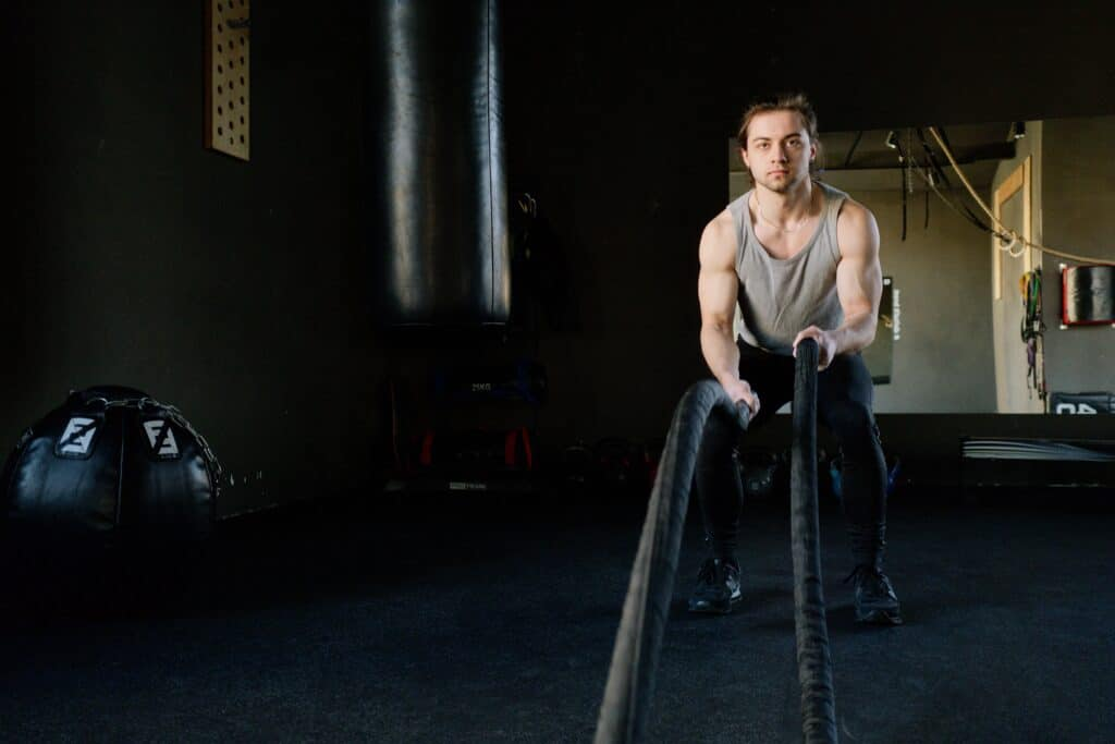 a man holding a rope wearing a black leggings