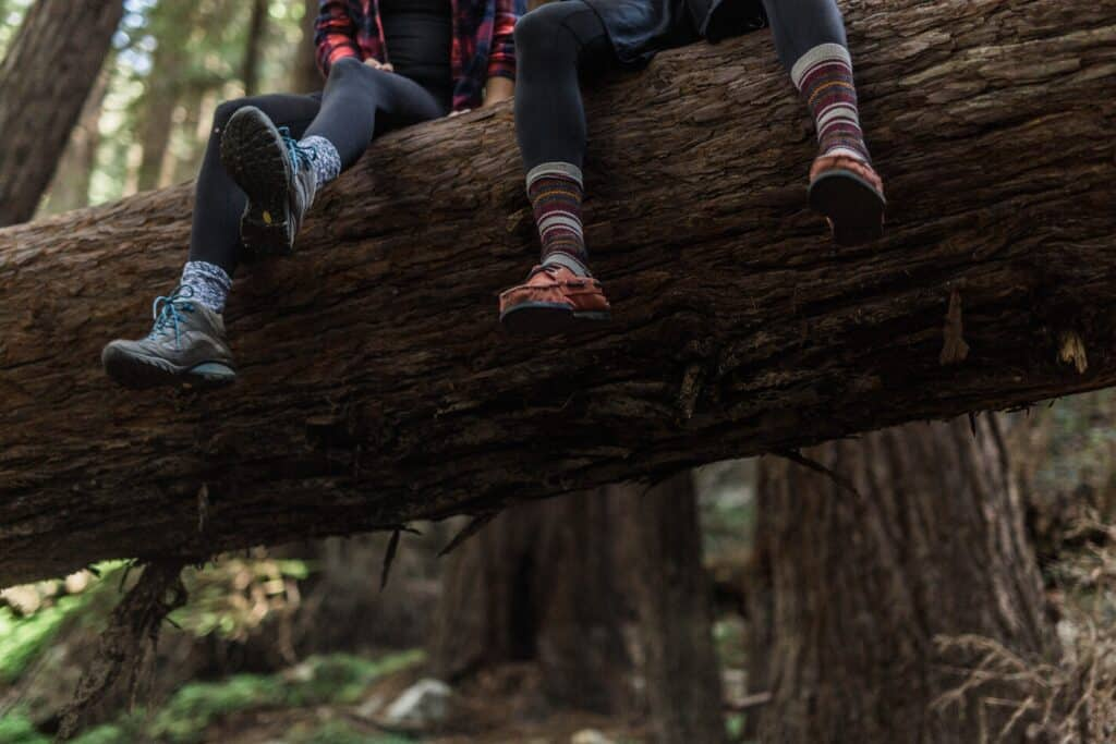 two people sitting on a tree wearing socks with leggings