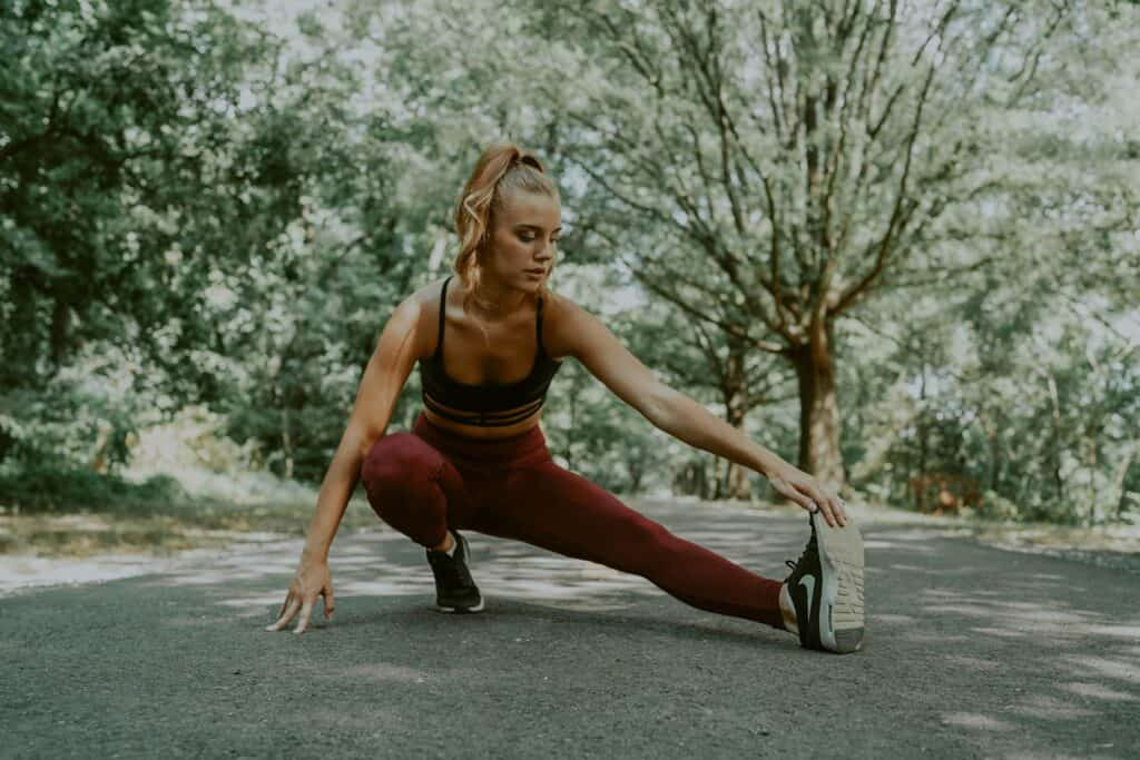 a woman stretching her toes wearing a maroon leggings