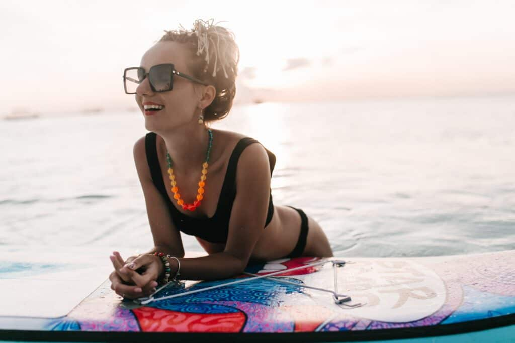 A woman leaning on a surf board on the beach