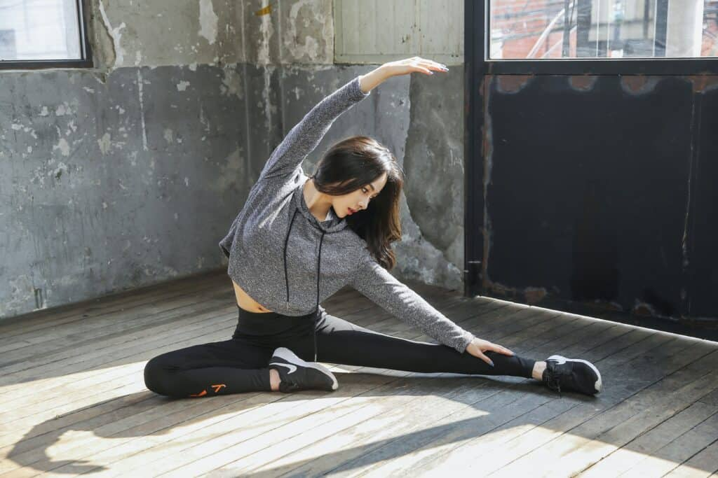 a woman stretching wearing printed leggings and bra