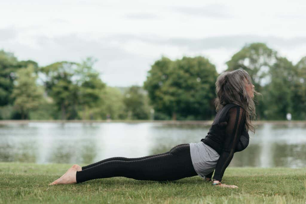 a woman stretching on the grass wearing black leggings