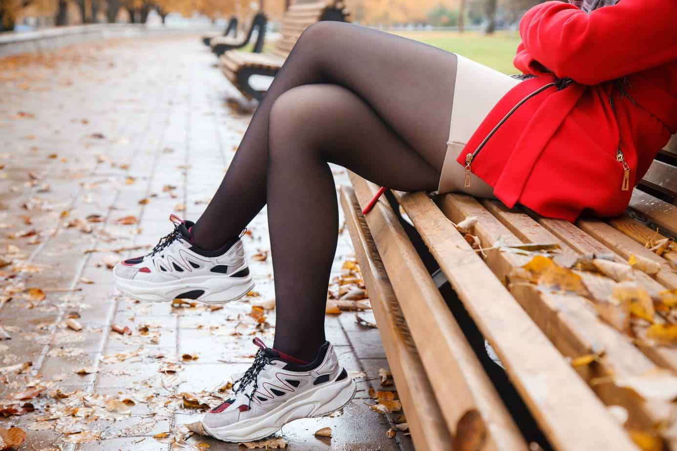a girl sitting on a bench wearing stockings