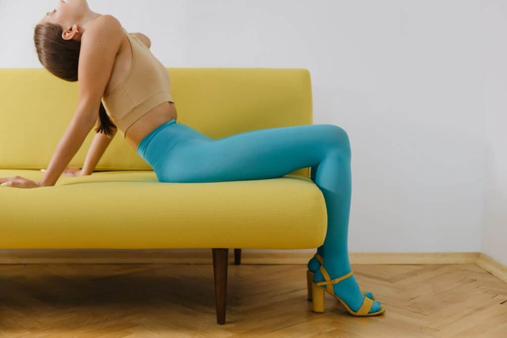 a woman sitting on a chair wearing a turquoise tights