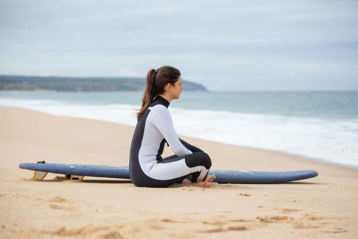 a woman sitting beside a surfboard wearing black and white wetsuit