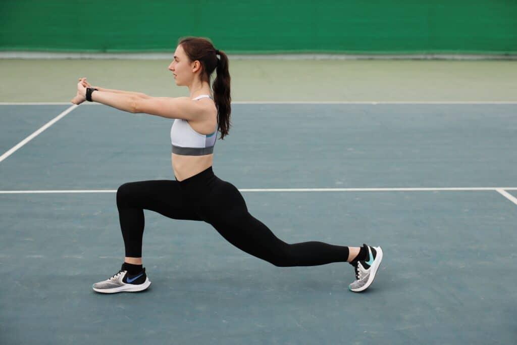 A woman doing lunges while wearing black leggings