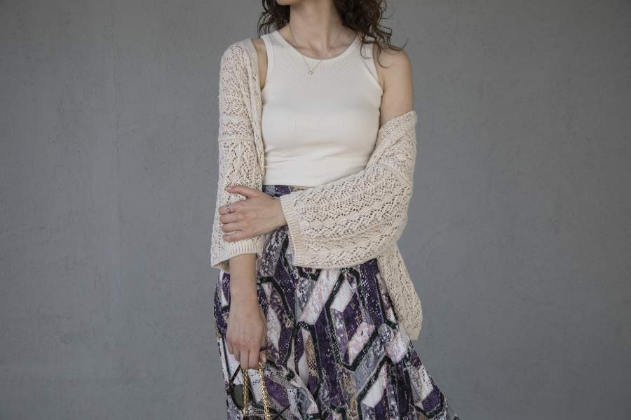 Woman wearing a knitted cardigan and a printed skirt